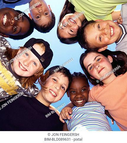 Smiling children hugging in circle