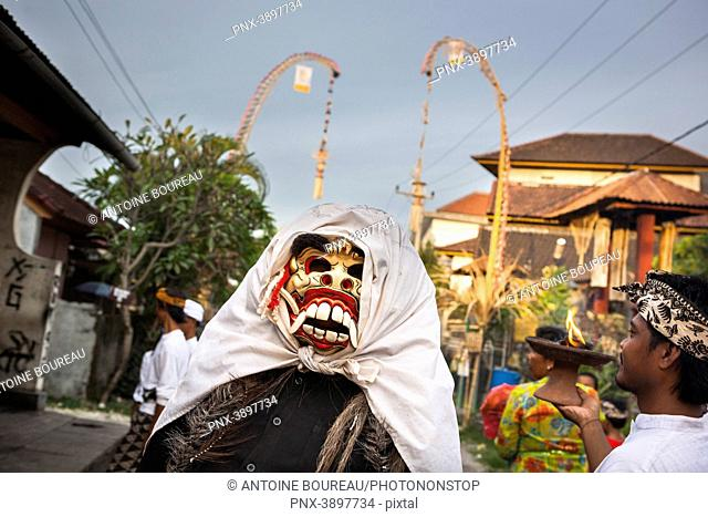 Child wearing a mask at a parade for the Hindu Kuningan ceremony in Bali, Indonesia