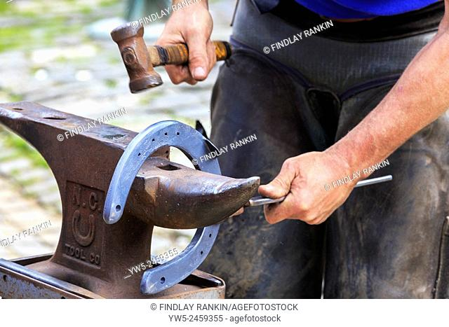 Farrier making a horseshoe and moulding it over an anvil while it was still red hot. Pollok Park, Glasgow, Scotland, UK