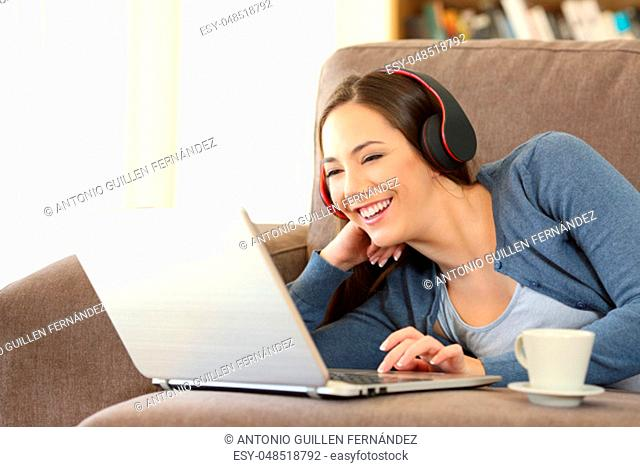 Happy woman wearing headphones watching media content on a laptop lying on a couch at home