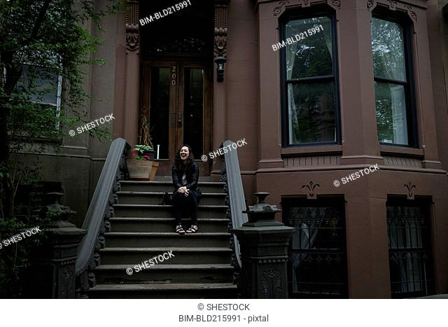 Caucasian woman sitting on townhouse front stoop