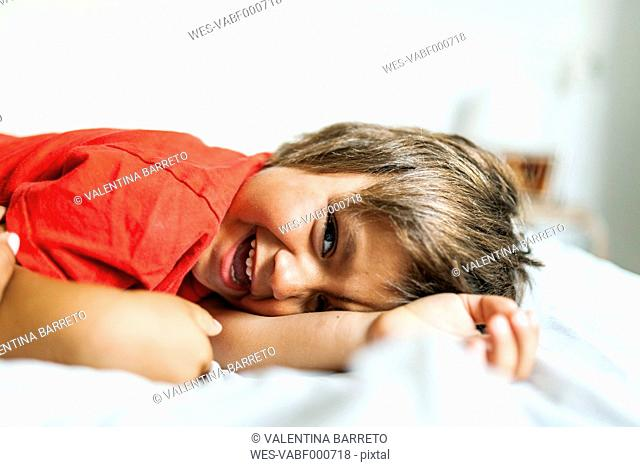 Portrait of smiling little boy lying on bed