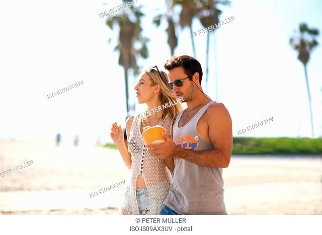 Couple strolling and sharing frozen yoghurt at Venice Beach, California, USA
