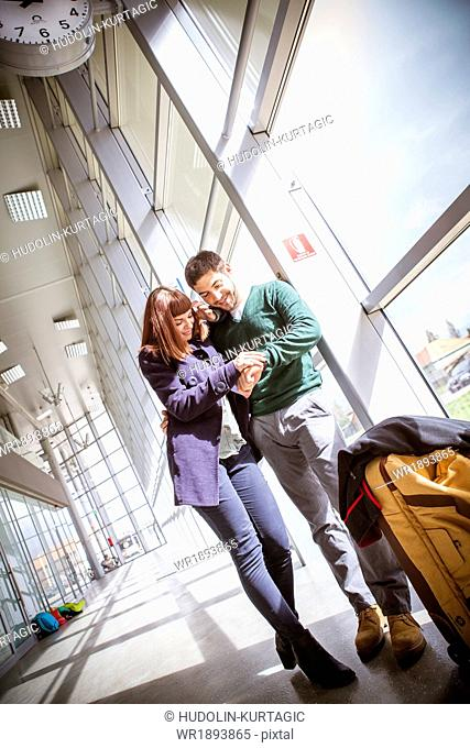 Young couple in airport building checking the time