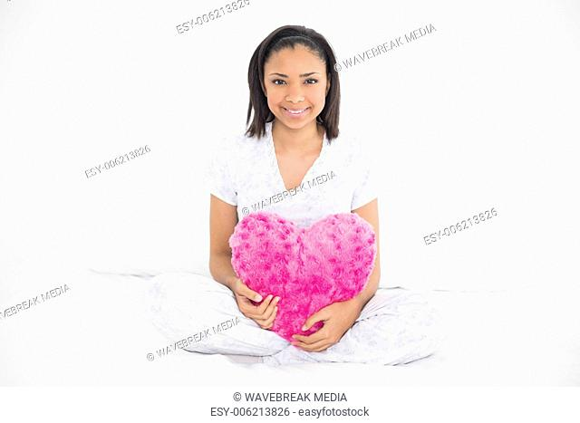 Pleased young dark haired model holding a heart-shaped pillow