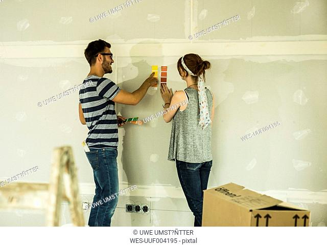 Couple holding colour samples at blank wall