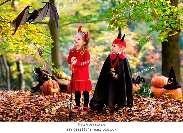 Two funny kids wearing devil and vampire costume with red horns and trident trick or treating on Halloween. Children dressed up as witch play in autumn park