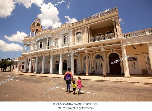 Mother and children walking in front of the Ferrer Palace-Palacio Ferrer in Plaza de Armas Square, Cienfuegos, Cuba, West Indies, Central America