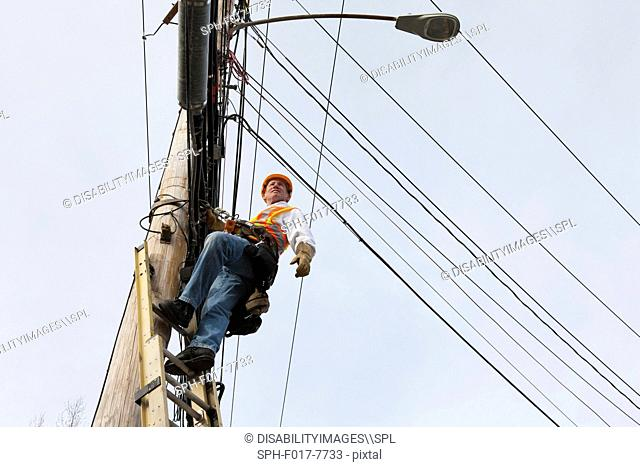 Communications worker standing on ladder on power pole