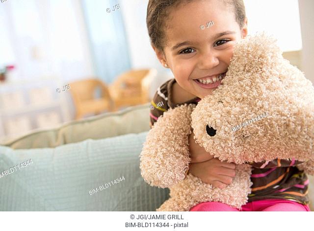 Hispanic girl hugging teddy bear on sofa