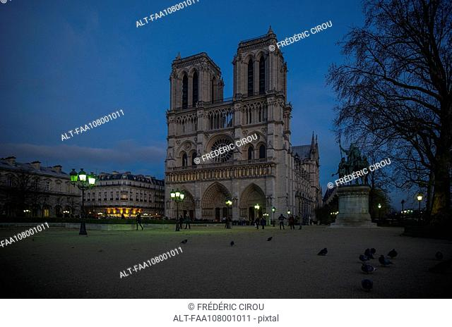 France, Paris, western facade of Notre Dame Cathedral at twilight