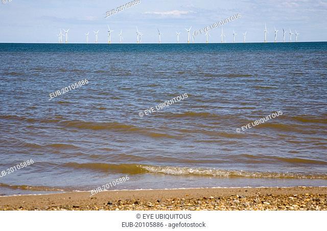 Wind Farm offshore on the horizon showing turbine blades