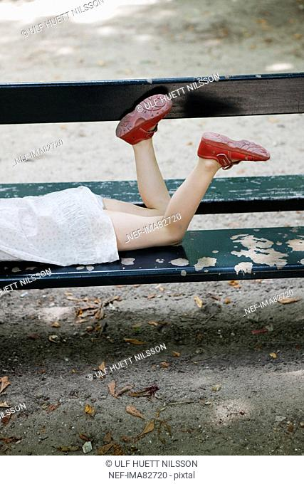Girl lying on a bench, France