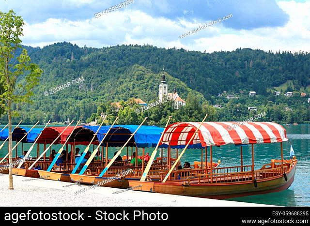 SLOVENIA, BLED - JULY 15, 2019: Traditional lake boats. Beautiful mountain lake in summer with small Church on island and alps in the background