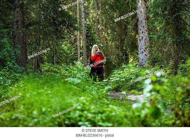 Caucasian woman using binoculars in forest