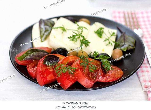 White cheese with tomatoes, green and black olives, basil, coriander and olive oil on the black plate