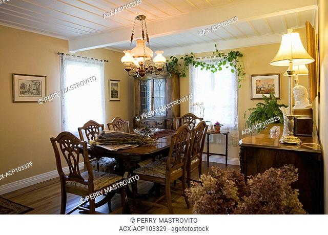 Antique dining table, chairs and furnishings in the dining room of an Old Canadiana cottage style (circa 1866) Residential home, Quebec, Canada