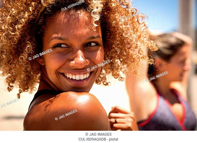 Young woman with curly hair looking over shoulder