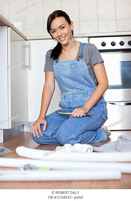 Woman working on pipes in kitchen