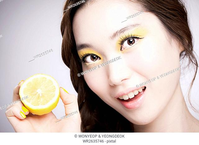 Portrait of young smiling Korean woman in yellow eye shadow posing with lemon