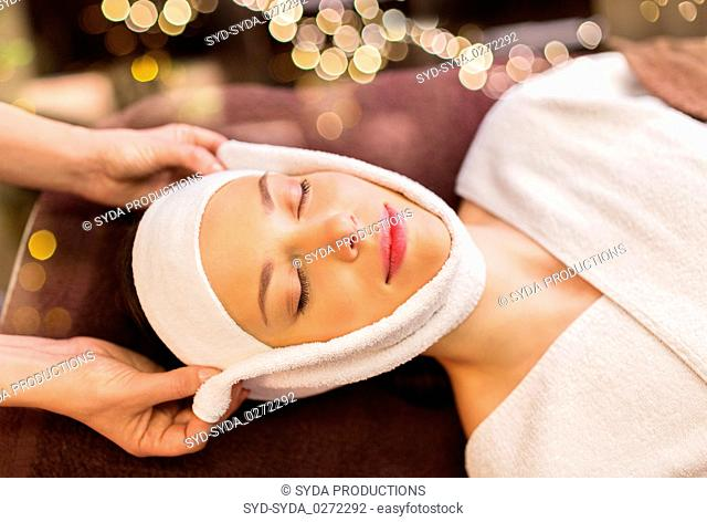 woman having face massage with towel at spa