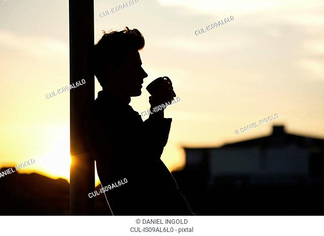 Young man leaning against post, drinking coffee, sunset