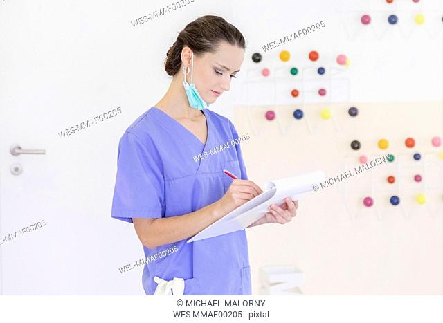 Female dentist filling in medical record
