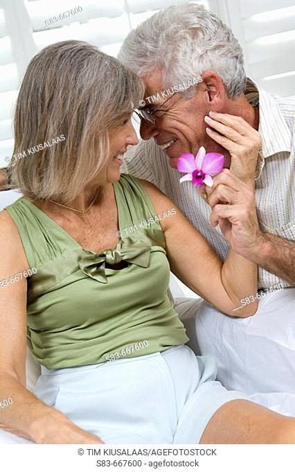 Senior couple being romantic with flower