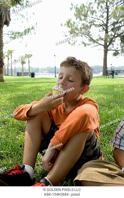 Boy eating a cupcake at a park