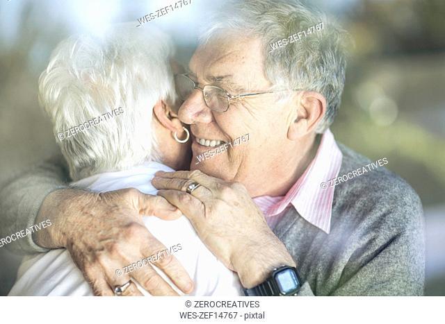 Happy senior couple hugging behind windowpane