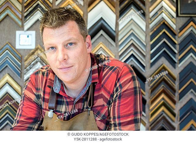 Goirle, Netherlands. Mid adult male craftsman and picture framemaker, portrait inside his workshop front office