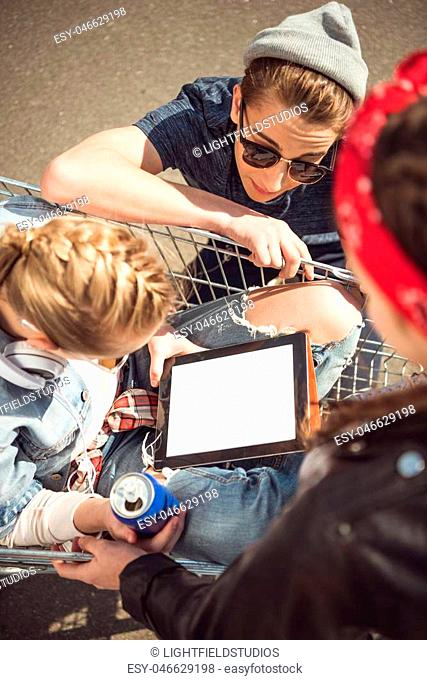 High angle view of friends looking at blonde girl sitting in shopping cart with digital tablet
