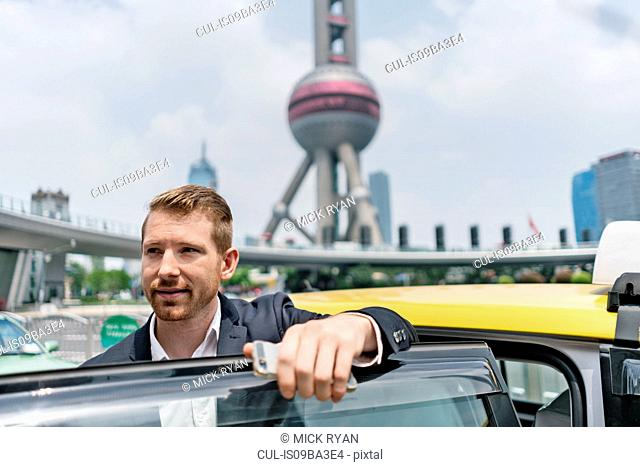 Young businessman getting out of yellow cab at Shanghai financial centre, Shanghai, China