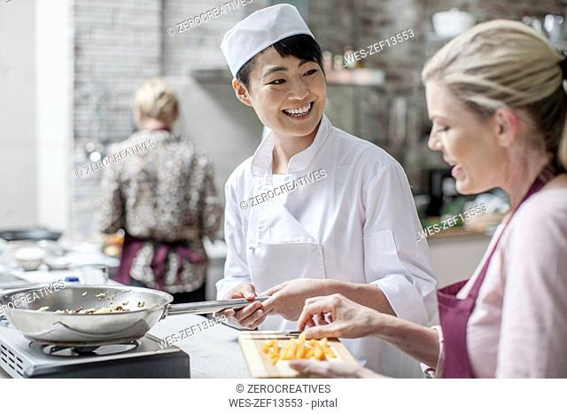 Female chef smiling at student in cooking class