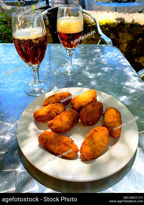 Croquettes serving with two glasses of beer in a terrace. Spain