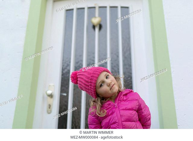Young girl wearing pink winter jacket and cap, standing in front of entry door