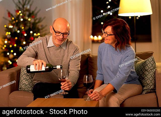 happy senior couple drinking red wine on christmas