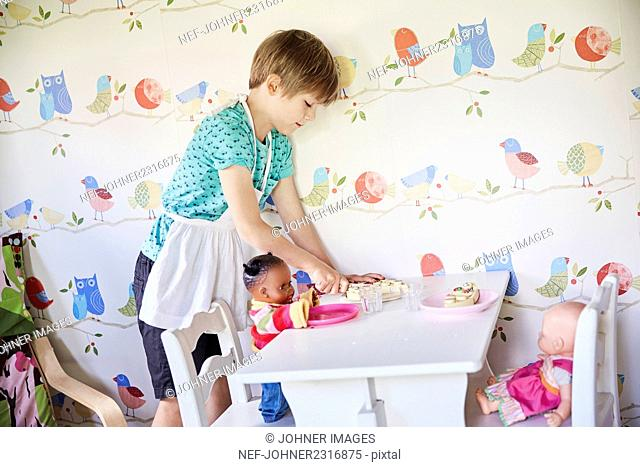 Boy serving toy cake to dolls