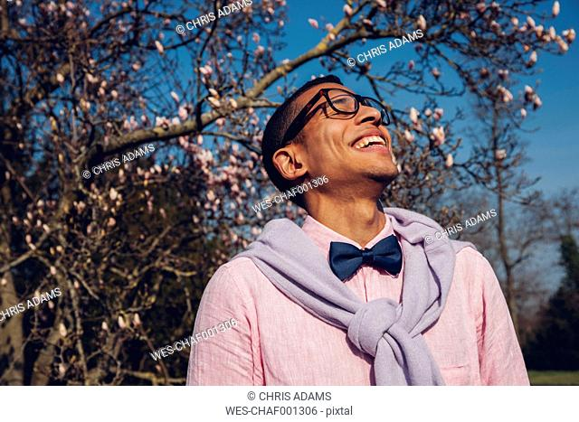 Young man in park in spring, wearing bow tie