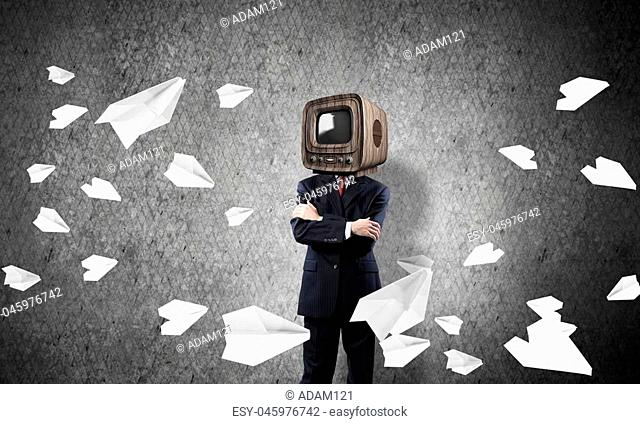 Businessman in suit with old TV instead of head keeping arms crossed while standing among flying paper planes and with gray dark wall on background