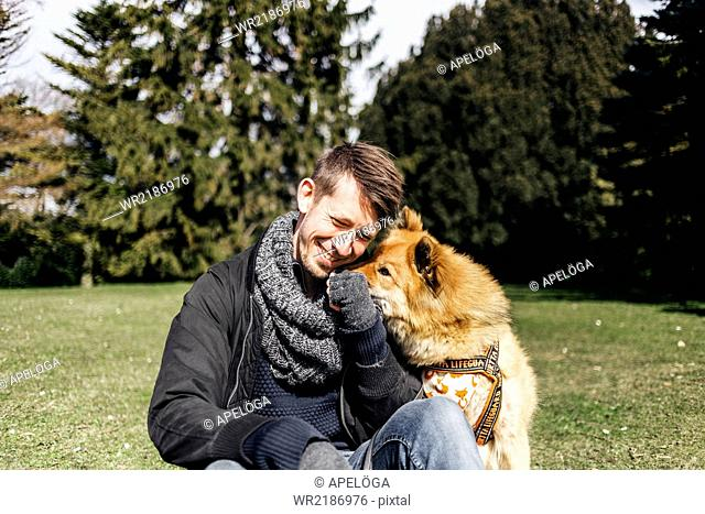 Happy man playing with Eurasier in park