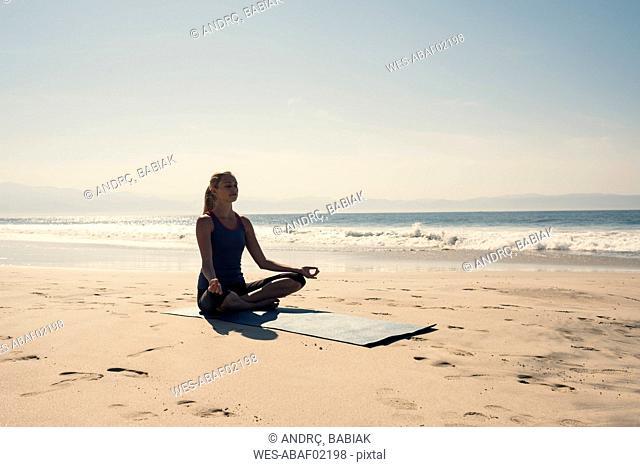 Young woman exercising yoga at a beach