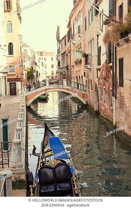 Gondola adorned with decorative ornaments moored on a narrow canal, venice, veneto, Italy, Europe