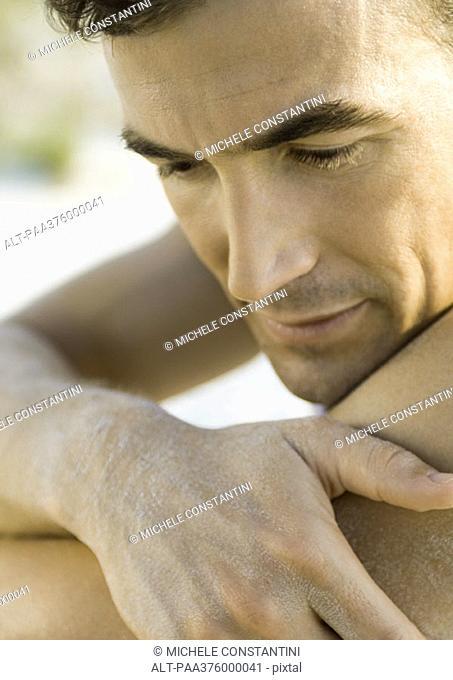 Man resting face on shoulder, close-up