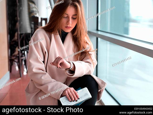 Young woman in international airport, waiting for her flight, checking her wrist watch and looking upset or worried. Arrival, missed