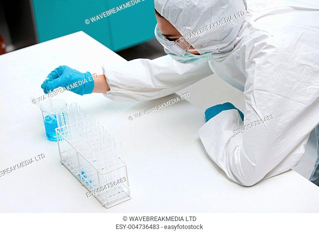 Protected science student pumping liquid with a pipette