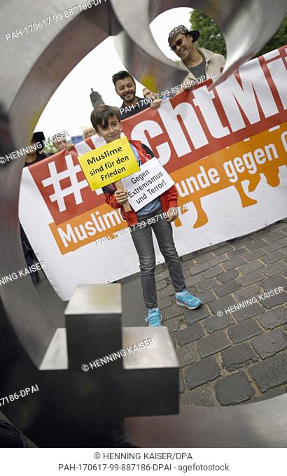 Participants hold signs during a peace march by Muslims against Islamist terrorism in Cologne, Germany, 17 June 2017.Several hundred people demonstrated under...