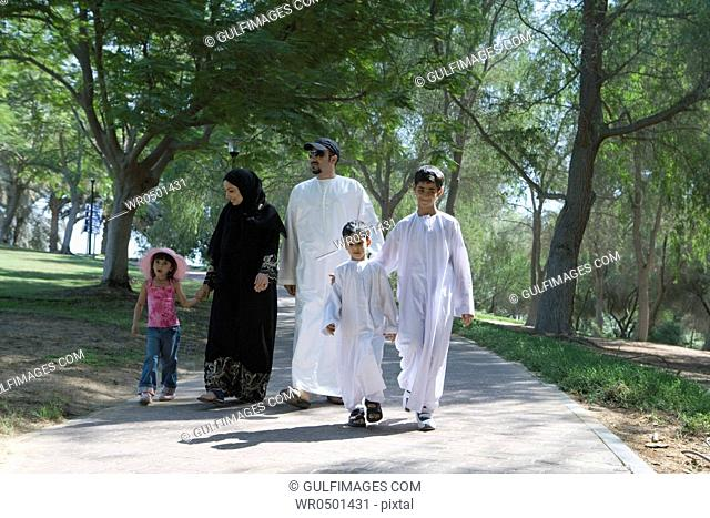 Father and mother with children walking in park