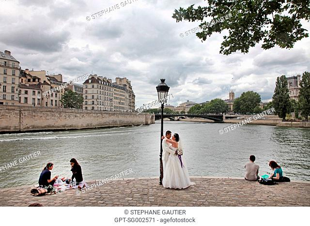CHINESE BRIDE AND GROOM POSING FOR THEIR WEDDING PHOTO AMIDST THE PEOPLE RELAXING AND PICNICKING ON THE POINT OF ILE SAINT-LOUIS, PARIS 75, FRANCE