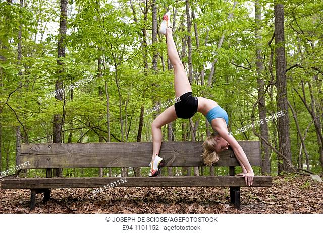 A young blond woman doing a yoga back bend posture on a wooden bench in a park